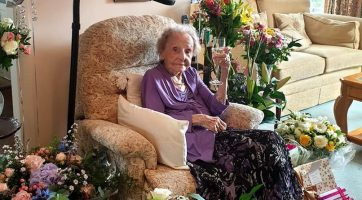 Joan enjoying a glass of champagne surrounded by all her flowers, gifts and cards
